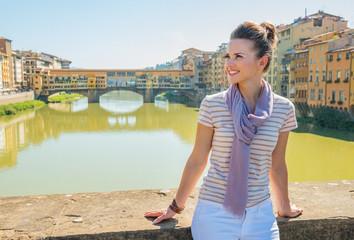 Woman sitting on bridge overlooking ponte vecchio  in florence