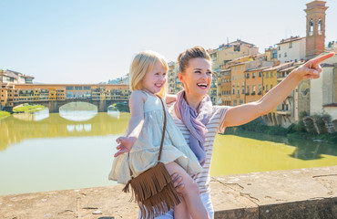 Happy mother and baby girl standing on bridge in firenze