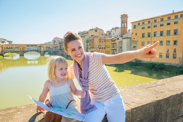 Happy mother and baby girl with map sitting on bridge in firenze
