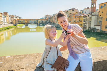 Happy mother and baby girl checking photos in camera in firenze