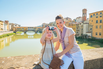 Mother and baby girl taking photo on bridge in firenze