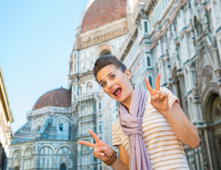 Portrait of funny  woman showing victory gesture  in florence