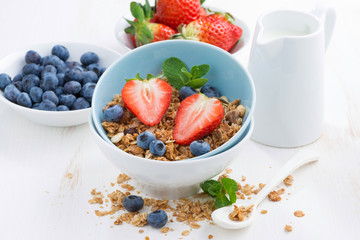 healthy food - granola, fresh berries and milk on white table