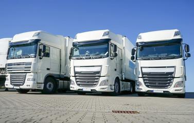 Drei weiße Lastkraftwagen im Depot einer Spedition