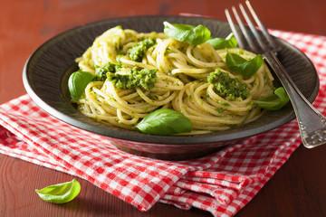 spaghetti pasta with pesto sauce over rustic table