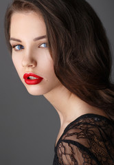 Portrait of beautiful brunette woman in black dress and red lips