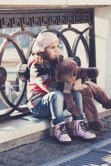 little girl sits at a fencing and holds a toy bear in hand