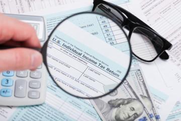 USA 1040 Tax Form 1040 seen via magnifying glass