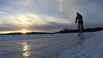 Winter cycling along ice road on big lake