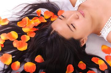 Oriental girl posing in studio lying among petals
