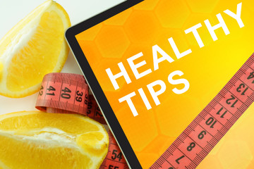 Tablet with words healthy tips and measuring tape