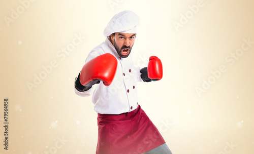 Chef fighting with boxing gloves over white background - 79564958