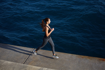 Young woman with fitness body running at the seaside