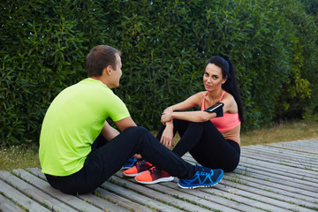 Beautiful sport couple resting after workout sitting in the park