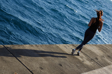 Woman with fitness body running at the coastline next to ocean