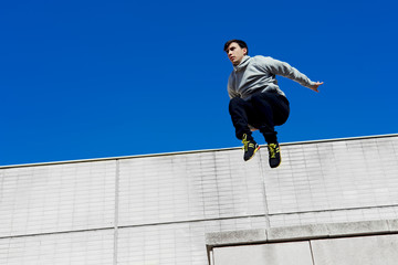 Young tracer athlete jumping over building roof against blue sky