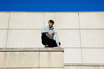 Young male traceur sitting on the edge of a high building