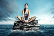 Woman relaxes on a rock in the ocean