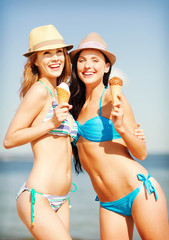 girls in bikinis with ice cream on the beach