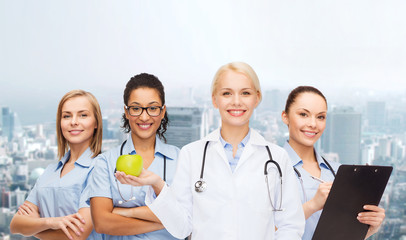 smiling female doctor and nurses with green apple
