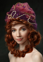 Beautiful red-haired girl in a headdress. Hair braided.