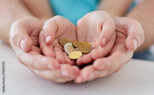 close up of family hands holding euro money coins - 79567735