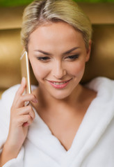 beautiful young woman with smartphone at spa