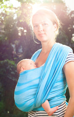 Woman with newborn baby in sling
