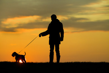 Silhouette of man and dog
