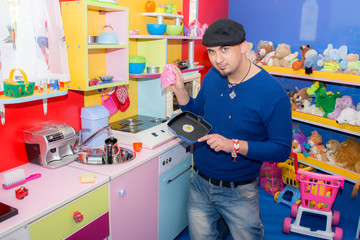 Young man in the kitchen cooking in nursery