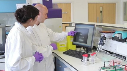 Two Scientist looking at DNA on computer screen
