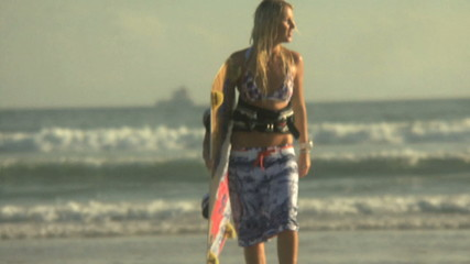 LS PAN OF  A YOUNG WOMAN WALKING FROM THE SEA CARRYING A SURFBOARD