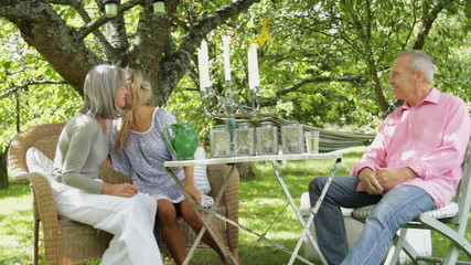 Parents and daughter around table talking in garden