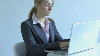 WS PAN UP OF A YOUNG BUSINESSWOMAN USING A LAPTOP