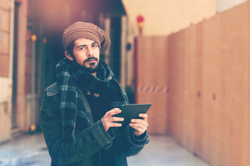 Stylish man enjoying the free internet using tablet in warm tone