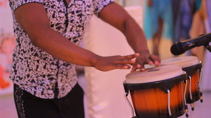 Young male percussionist playing cuban drums against black