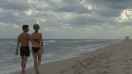 Couple holding hands walking along a beach