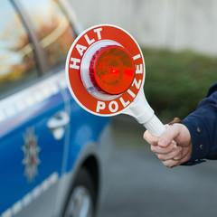 polizist zeigt die haltekelle