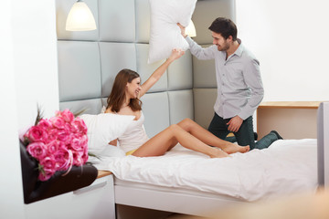 Couple Playing and Having a Pillow Fight in Bed