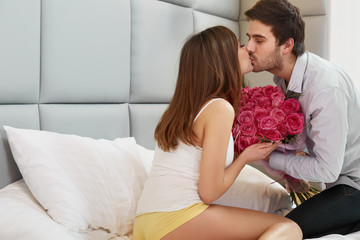Kissing Couple. Man Gives Flowers to his Girlfriend