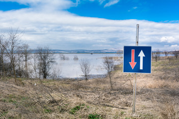 Flood - a natural phenomenon. Beautiful blue sky and road sign