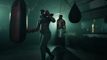 Group of Boxers Training in a Group. Female in the foreground.Male skipping in the background