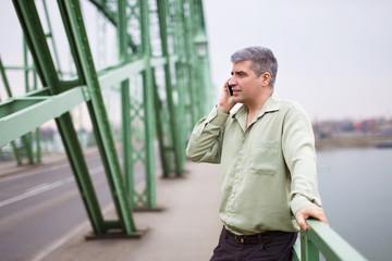 Young entrepreneur calling at bridge