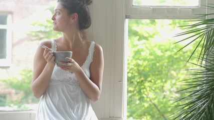 Female eating breakfast out of bowl sitting in bedroom window