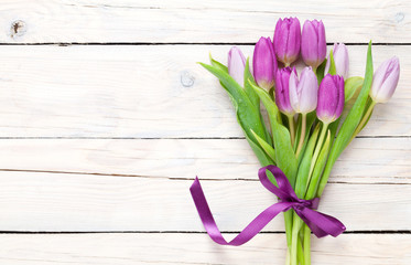 Purple tulip bouquet over wooden table