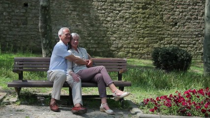 Senior couple embracing on bench in park, Istanbul, Turkey