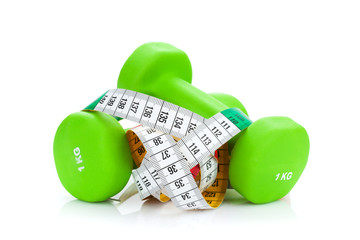 Two green dumbells and tape measure. Fitness and health