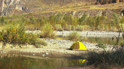 Yellow tent on the autumn river bank
