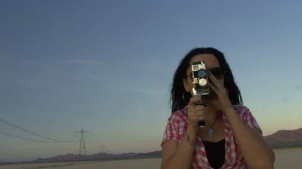 Female in desert using a cine camera