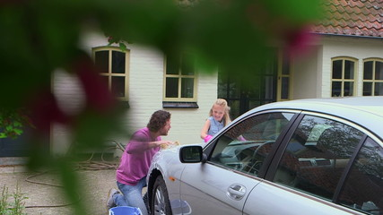Daughter helping father to wash car